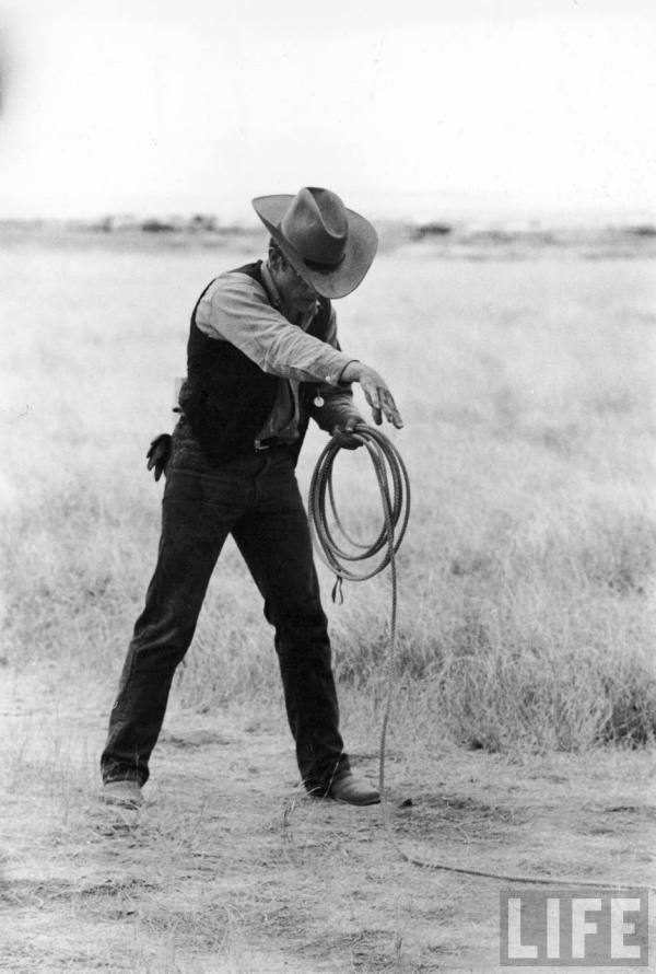 "Actor James Dean clad in Western garb for his role, holding a coiled rope, on location for the movie ""Giant."""