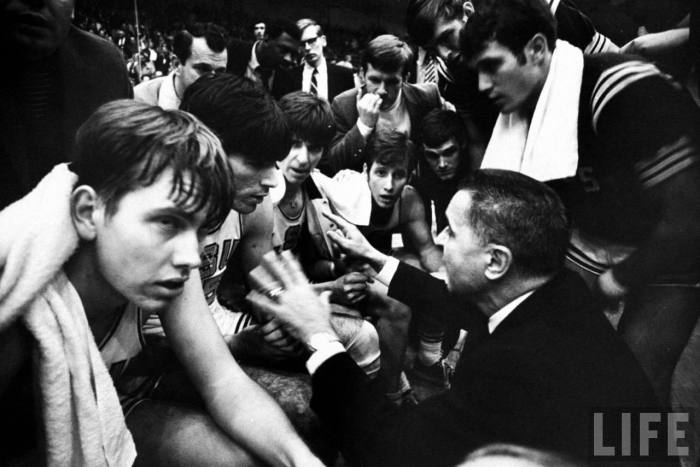 Louisiana State Univ. basketball team (including Pete Maravich in middle of bench) listening to Coach Press Maravich during game.  --Ca. 1969.