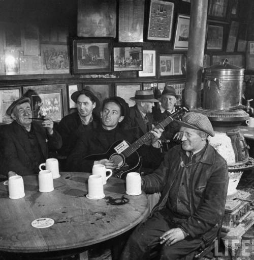 Activist folk musician Woody Guthrie playing in the famed McSorley's Pub.  -New York 1943