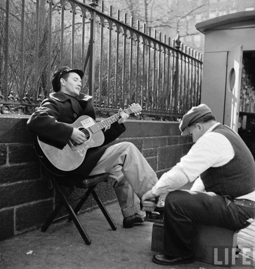 Folk singer Woody Guthrie playing his guitar while getting a shoeshine.  -New York 1943
