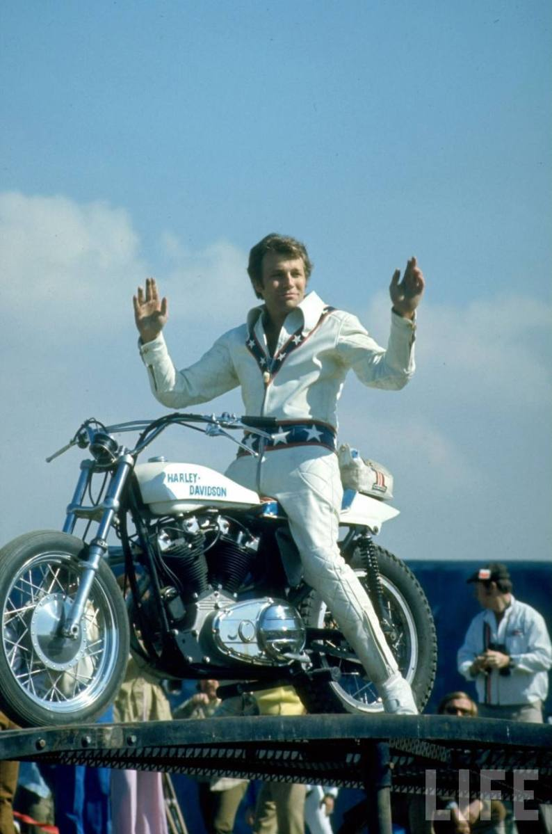 Motorcycle daredevil Evel Knievel poised on his Harley-Davidson.  1971