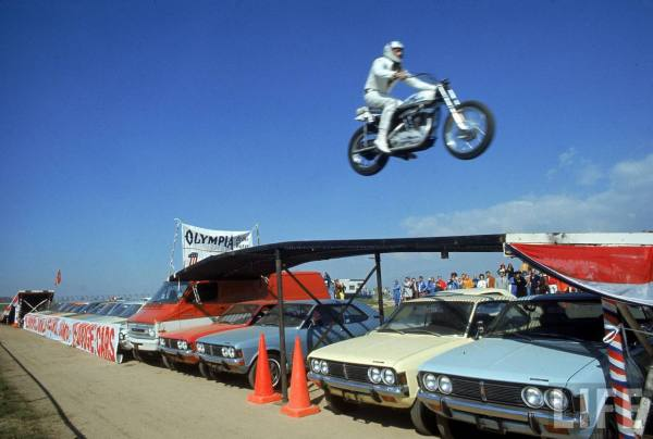 Daredevil motorcyclist Evil Knievel in mid jump over a row of cars.  March 1971