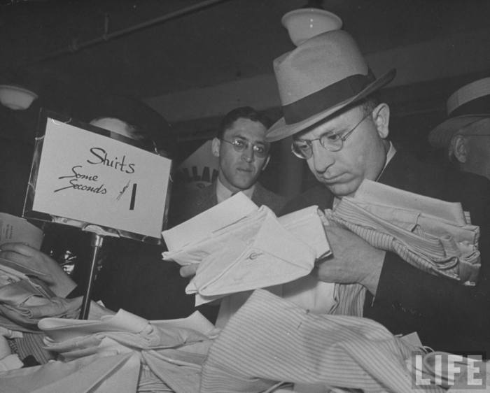 Intense male shopper pouring over SHIRTS $1 counter during Dollar Day sale in Filene's basement which has racked up a record of $15,000 worth of sales in men's shirts for the day. --Boston, MA 1938