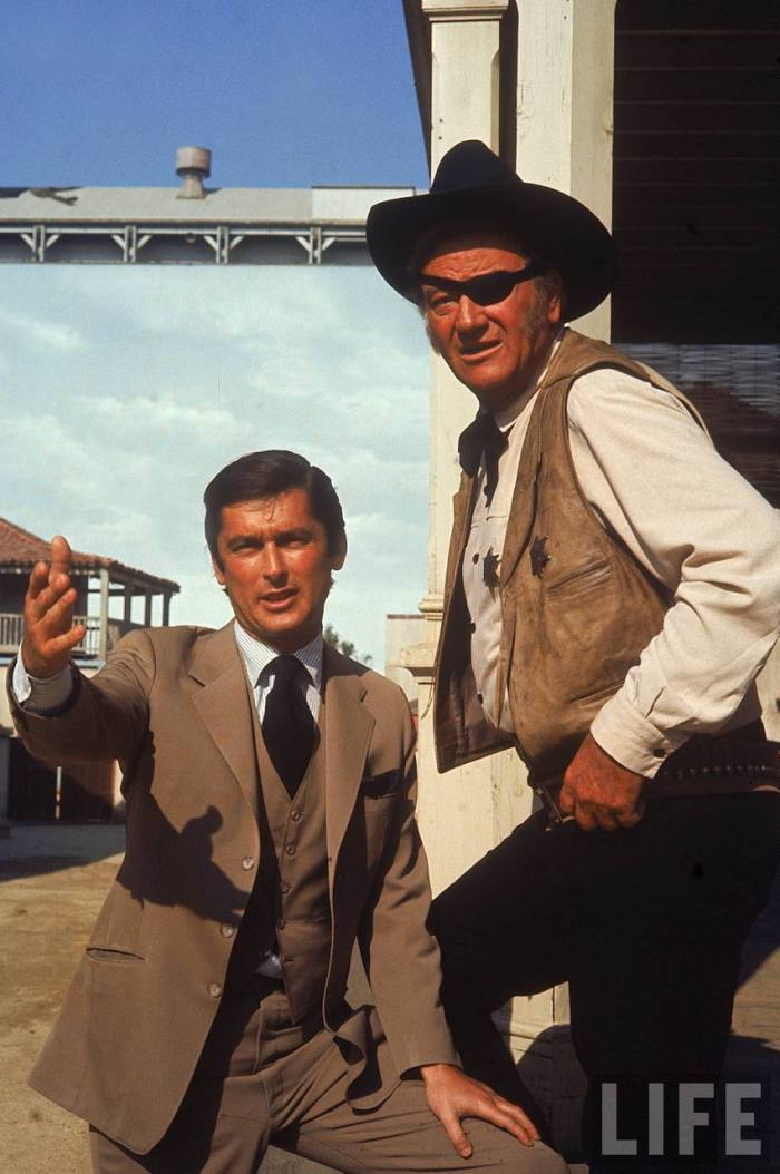 Paramount Vice Pres. Robert Evans on movie set with actor John Wayne.