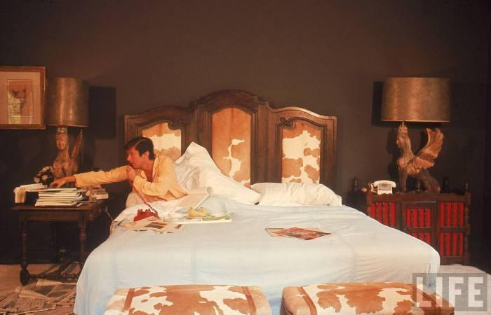Film director Robert Evans talking on phone while in bed at home-- Beverly Hills, CA 1968.