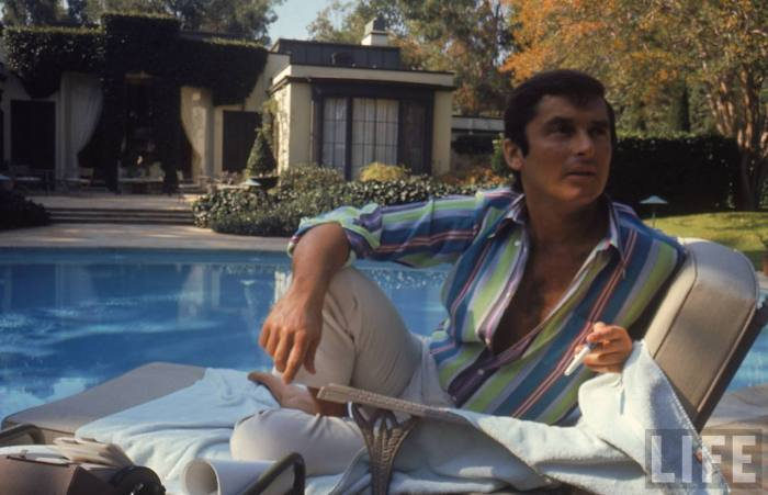 VP of Paramount Pictures Robert Evans studying his script by the pool at his home-- Beverly Hills, CA 1968.