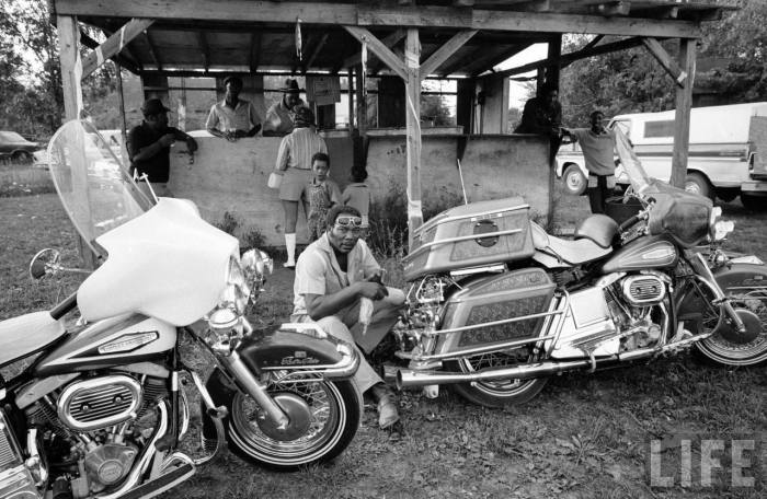 Black motorcyclist of the Big Circle Motorcycle Association sitting between pair of Harley Davidson cruising bikes-- circa 1971.