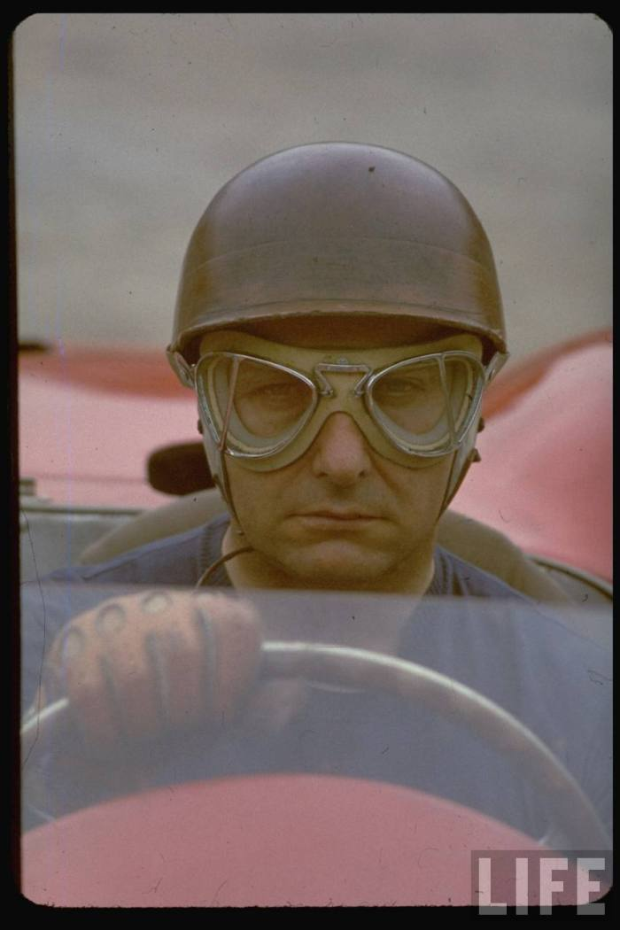 Argentine auto racing legend Juan Manuel Fangio sitting at wheel of race car at Las Mans.