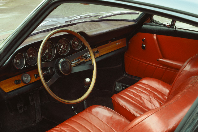One of the most influential cars of the twentieth century - the rear engined Porsche 911 began production in 1964. The wood and leather trimmed interior of the first 911 model is perfectly appointed.