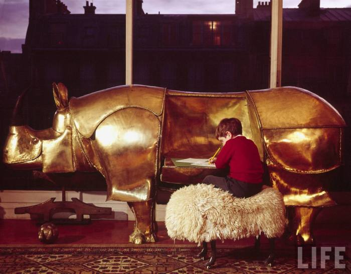 Large brass rhinoceros designed by Francois-Xavier Lalanne with folding sides being used as a desk by a little boy, also has a piggy-bank head with coin-drops in the ears --1967.