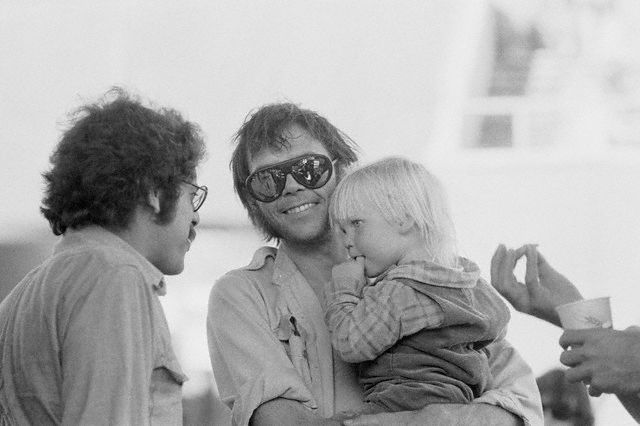 San Francisco, July 15th, 1974 --- Neil Young holds his son Zeke at a Crosby, Stills, Nash & Young concert. --- Image by © Neal Preston