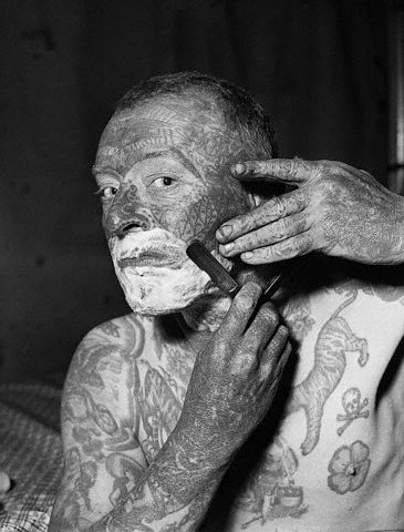 """Edward Vanderwerer, known better as """"Tattoo Van"""" a member of the World of Mirth Carnival, as he shaved before his appearance as a carnival attraction, May 8th, at Alexandria, Va. Vanderwerker is compelled to shave very closely in order that his face maintain the detail of the tattooing. He has also had some tattooing done on his scalp --1937."""