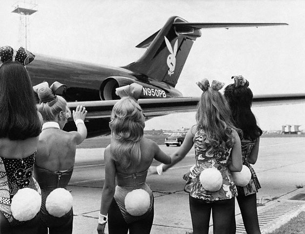Playboy Bunnies wave as Hugh Hefner's private jet lands in London-- 1970.