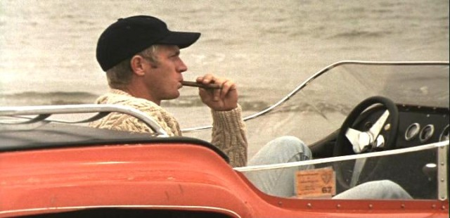 "Steve McQueen enjoying a cigar behind the wheel of the ""TCA"" dune buggy."