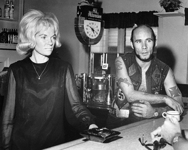 "Case involving members of ""Outlaws"" motorcycle club, who are accused of nailing a female member of their club to a tree for holding out $10.  Mrs. Bertha (Kitty) Randall and tattooed biker Donald ""Deke"" Tanner inside her bar  --West Palm Beach, FL 1967."
