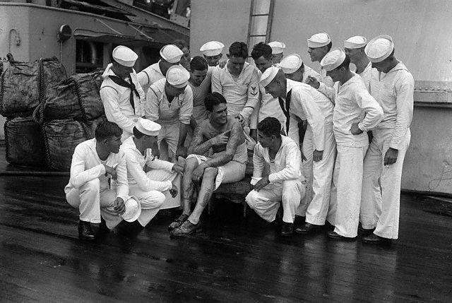 Storytelling time aboard the U.S.S. Texas found S.O. Buchanan, tattooed wonder of the crew, surrounded by shipmates --1928.