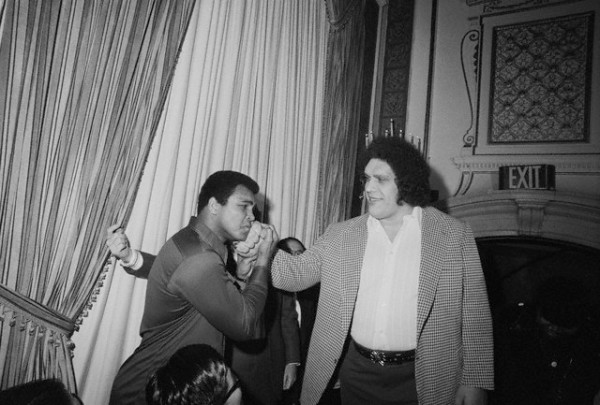 "March 25th, 1976-- New York.  Ali Meets a Giant.  When World Heavyweight Boxing Champion Muhammad Ali was in New York, March 25th, 1976 to meet Japanese wrestler Antonio Inoki, whom he will meet in a boxer versus wrestler match in Tokyo, June 26th, someone caught his eye --- it was seven-foot-four Andre, the Giant, a wrestler from France and friend of Inoki. The towering Asdre became the object of Ali's attention after he was through trading barbs with Inoki. Ali, so taken in by the man who made him look diminutive by comparison, literally bowed to Andre and then matched his hand against Andre's massive palm. All later placed ""The Giant's"" fist on his jaw -- glad he won't have to face such a blow."