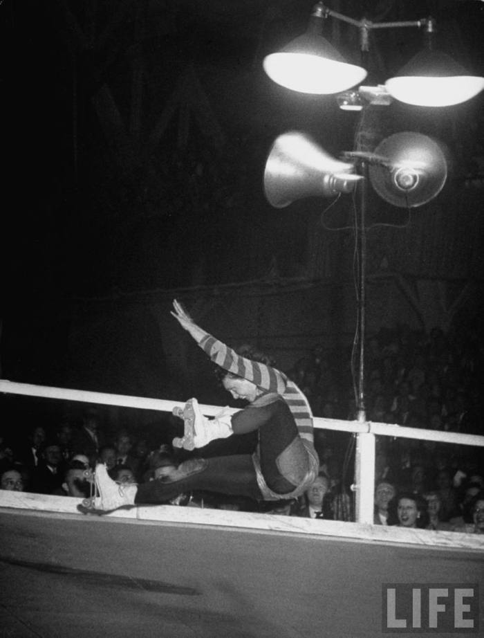 Travelling roller derby show of professional skaters shown in Chicago's Coliseum with skater Vivian Johnson falling after losing control on a corner.  Chicago, IL. 1948.