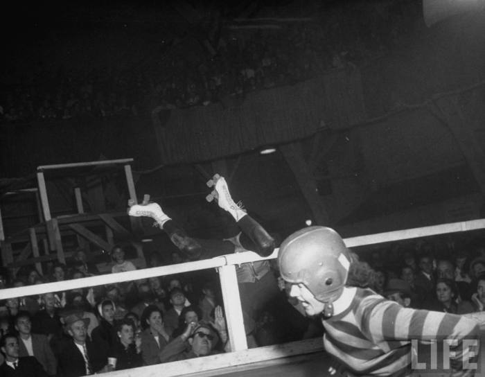 Travelling roller derby show of professional skaters shown in Chicago's Coliseum with skater Vivian Johnson (R) blocking and knocking another skater over the railing.  --Chicago, IL. 1948.