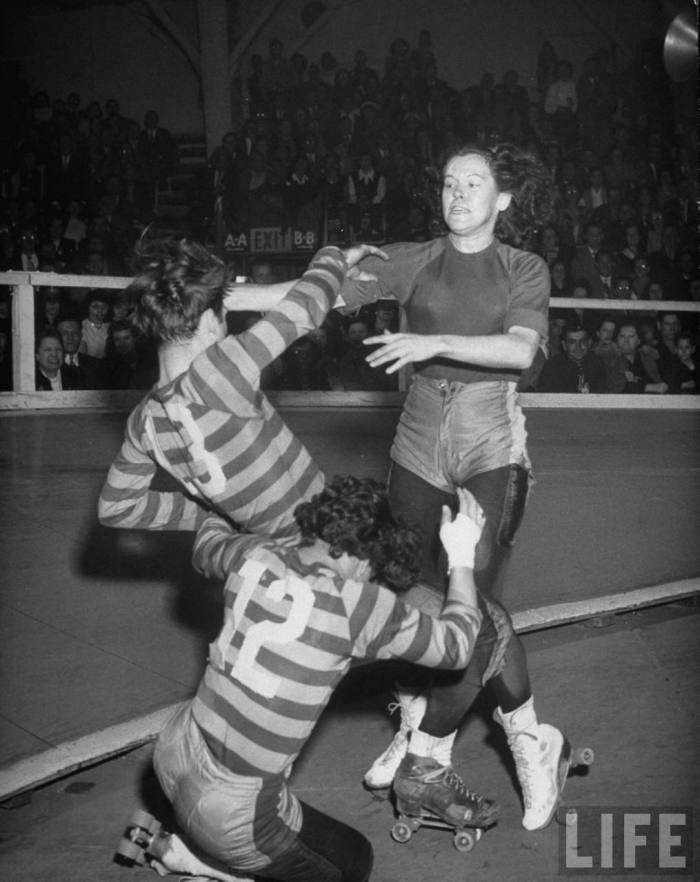 "Travelling roller derby show of professional skaters shown in Chicago's Coliseum with skater ""Toughie"" Brashun (L) fighting with opposing team member Gerry Murray (R) while another steps into the middle at an attempt to mediate.  Chicago, IL. 1948."