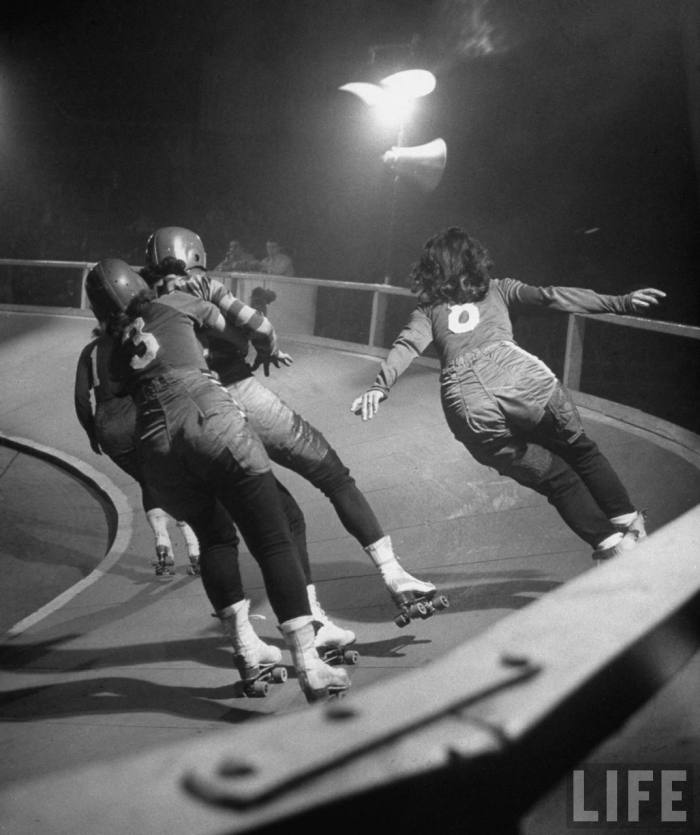 Travelling roller derby show of professional skaters shown in Chicago's Coliseum with skater at left holding another so that her team mate can pass on the right.  Chicago, IL. 1948.