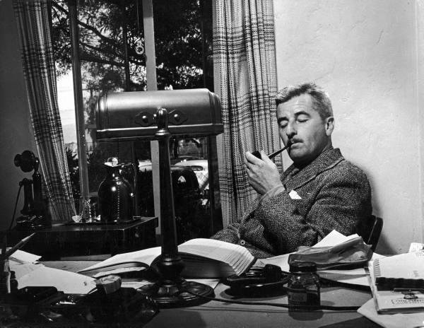 William Faulkner enjoying a smoke in his study.