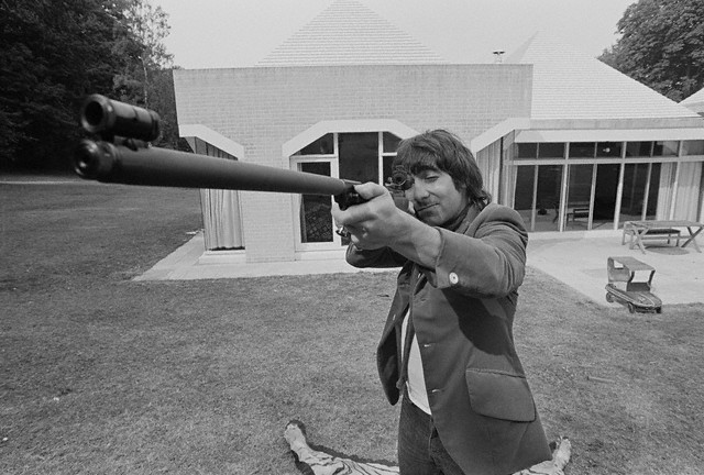 The Who's drummer Keith Moon aiming a gun in front of his new, modern house, ca. 1972.