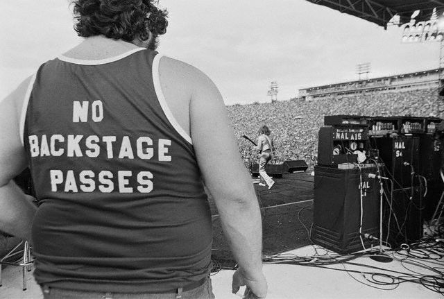 Roadie wearing  tank top that states-- NO BACKSTAGE PASSES.