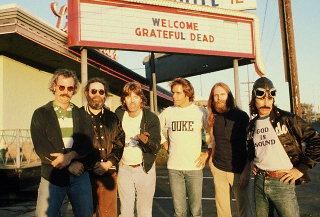 "The Grateful Dead-- Bill Kreutzman, Jerry Garcia, Mickey Hart (""God is Sound"" T-shirt), Phil Lesh, Bob Weir, and Brent Mydland."