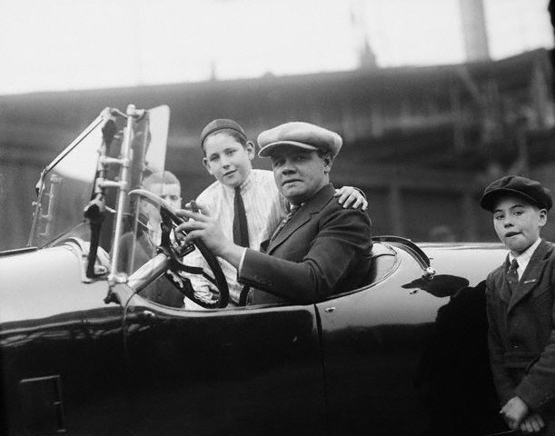 Original caption  -- The homerun king is an ardent motorist, often traveling from city to city in his car instead of going by train with the Yankees. Taking out some of his youthful admirers for a spin in his speedy Packard roadster after the game. -- April 28th, 1921.