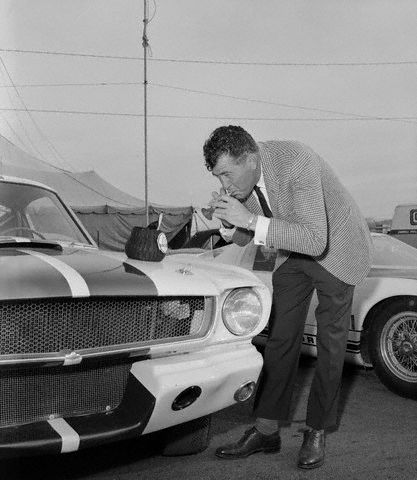 Carroll Shelby, whose Ford powered cars have been a constant contender in International racing, plays a toy flute to charm a toy Cobra out of its basket on the hood of his latest offering to the automotive world, the Mustang GT 350, at the first showing of the car- January 27th, 1965 in Riverside, CA.  The Shelby is a modified Ford Mustang Fastback, with a 289 Ford Cobra engine, front disc brakes, and improved suspension for road racing or high speed driving. -- Image by © Bettmann/CORBIS