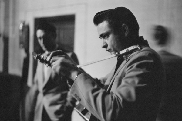 Johnny Cash tunes his guitar backstage in White Plains, New York, ca. 1959.