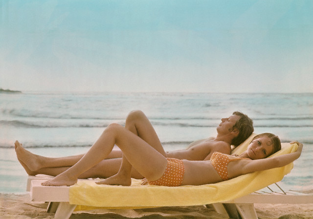 ca. 1968 --- Model Cheryl Tiegs at the beach in an orange bikini with white polka dots by Villager.