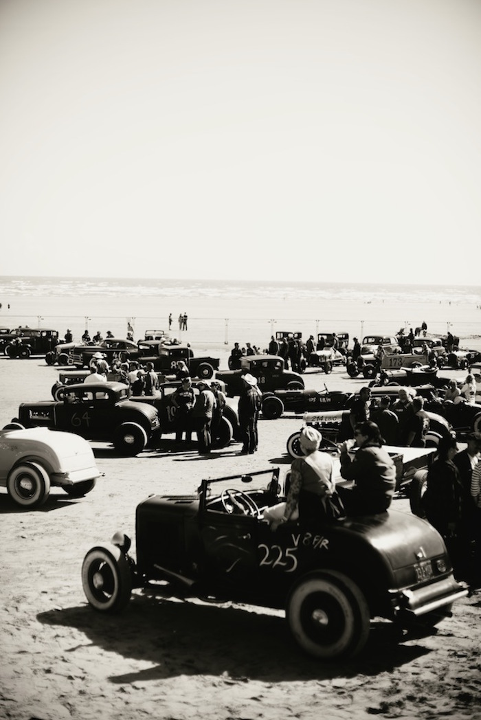 Vintage hot rods waiting to race on the sandy beach.